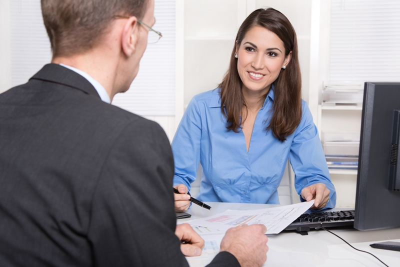 A woman and a man in a business setting conversing over documents.